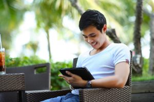 man using ipad smiling