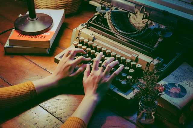 person writing on typewriter content marketing
