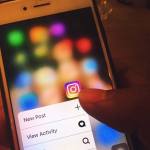 phone user holding Instagram icon on screen